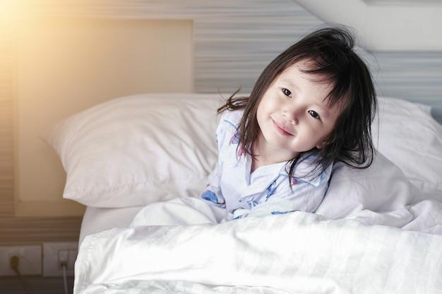 Asiatisches kleines mädchen wacht vom schlaf auf guten morgen zu hause