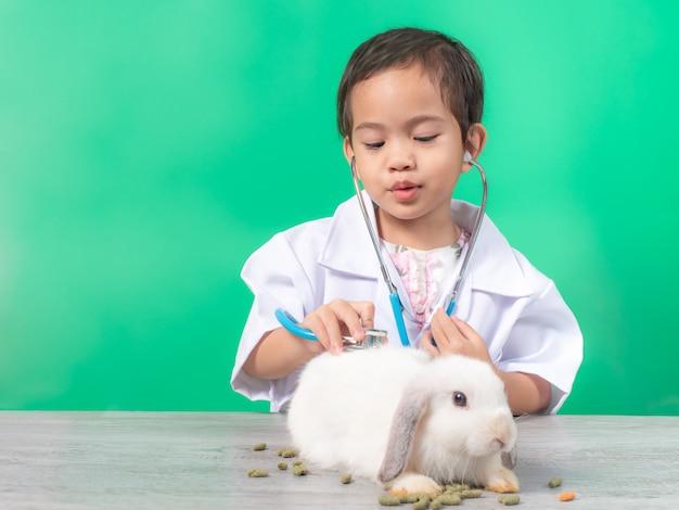 Asiatisches kleines nettes mädchen 3 jahre alte rolle, die tierarztdoktorbesetzung spielen.