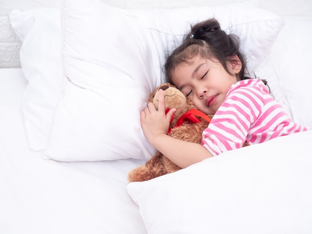 Asiatisches kleines nettes mädchen 6 jahre alt, pyjamas tragend und auf weißem kissen und bett schlafend.