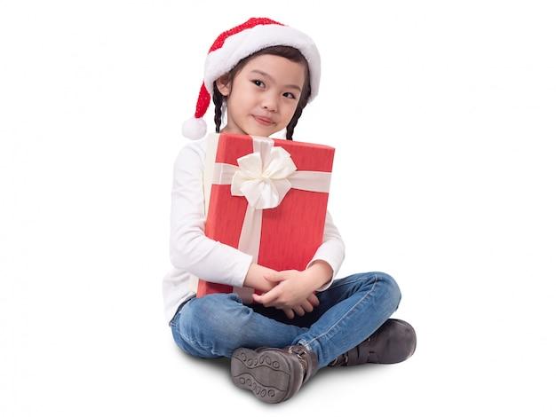 Asiatisches kleines nettes mädchen 6 jahre alte tragende santa claus-kappe, die rote geschenkbox lokalisiert sitzt und hält