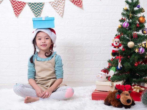 Asiatisches kleines nettes mädchen 6 jahre altes sitzen auf teppich und setzte eine geschenkbox ihren kopf in reinraum mit dem weihnachtsbaum ein.