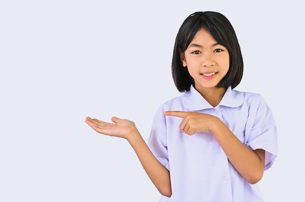 Asiatisches kleines schulmädchen, das etwas über ihrer hand und dem finger zeigt zeigt, kind, das lächeln zur kamera lokalisiert in weißer wand für show- oder ausstellungswerbung zeigt