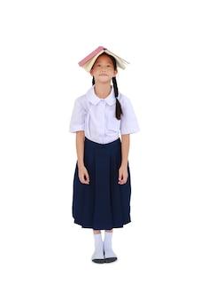 Asiatisches kleines schulmädchen des porträts in der thailändischen schuluniform, die mit offenem lehrbuch über dem kopf lokalisiert auf weißem hintergrund steht. in voller länge mit beschneidungspfad