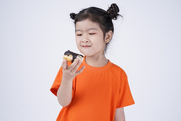 Asiatisches kleines süßes mädchen, das großen donut lokalisiert auf weiß isst