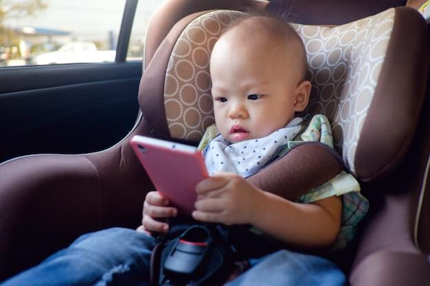 Asiatisches kleinkindbaby, das im autositz sitzt und ein video vom intelligenten telefon aufpasst