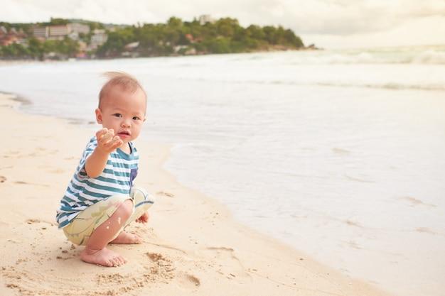 Asiatisches kleinkindbabykind am strand mit schmutzigen händen bedeckt mit nassem sand, wasser im freien aktivität auf sommerstrandurlaub mit kindern, sensorisches spiel mit sandkonzept