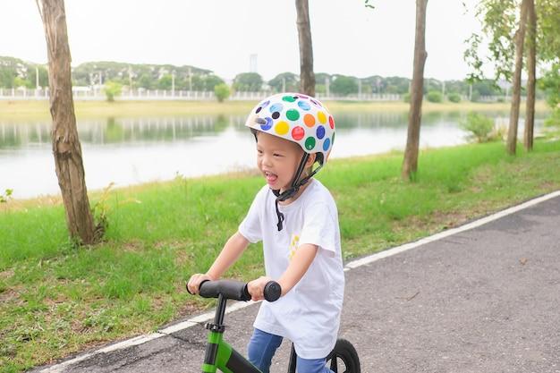 Asiatisches kleinkindjungenkind, das schutzhelm trägt, der lernt, erstes laufrad in sonnigem sommertag zu fahren