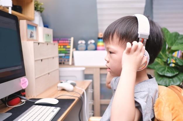 Asiatisches kleinkindjungenkind mit pc-computer, kleines kind zu hause, kindergarten geschlossen, fernunterricht, aktivitäten für kindergartenkonzept