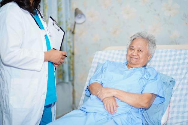 Asiatisches krankenschwesterphysiotherapeut-doktorgespräch mit älterem frauenpatienten am krankenhaus.