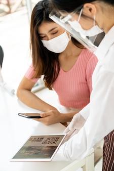 Asiatisches kundenscan-qr-code-online-menü von der kellnerin mit gesichtsmaske und gesichtsschutz. der kunde saß nach der coronavirus-covid-19-pandemie auf einem tisch zur sozialen distanzierung für einen neuen normalen lebensstil im restaurant
