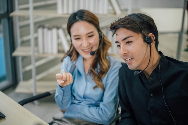 Asiatisches kundensupport-team mit headset, das im büro arbeitet.