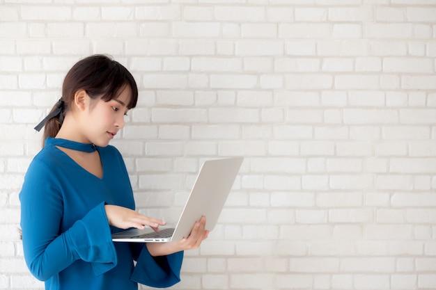 Asiatisches lächeln der jungen frau des schönen porträts unter verwendung des laptops, der am arbeitsplatz steht