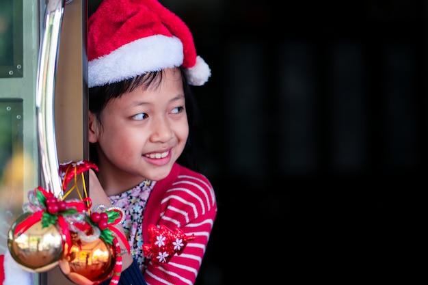 Asiatisches lächelndes schönes mädchen hinter tür
