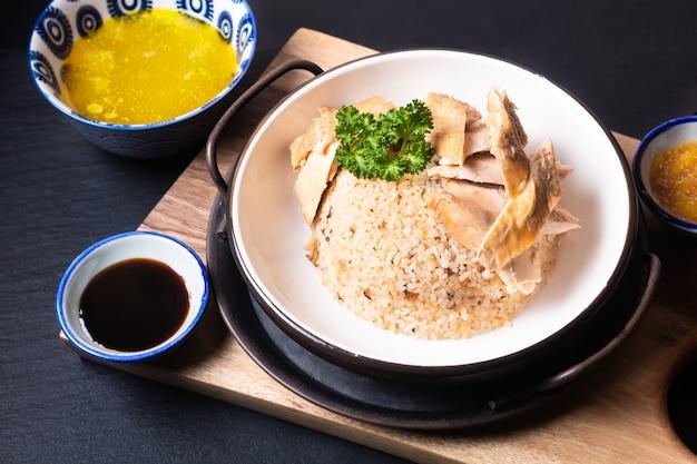 Asiatisches lebensmittelkonzept hainaner hühnerreis mit saurer und süßer sojasauce auf holzbrett mit schieferstein
