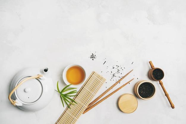 Asiatisches lebensmittelkonzept mit teesatz, essstäbchen, bambusmatte