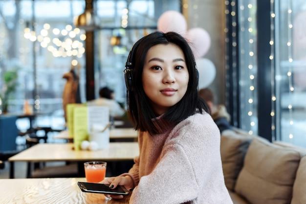 Asiatisches mädchen allein in der stadt sitzt in einem café und hört musik. musik an einem öffentlichen ort genießen