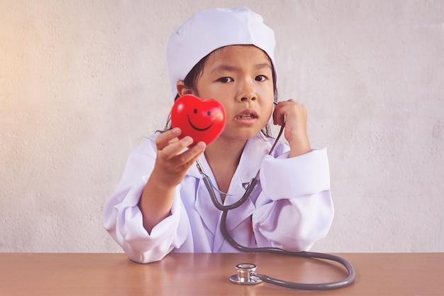 Asiatisches mädchen, das als gesundes herz der doktorpflege spielt