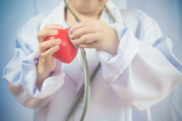Asiatisches mädchen, das als gesundes herz der doktorsorge spielt