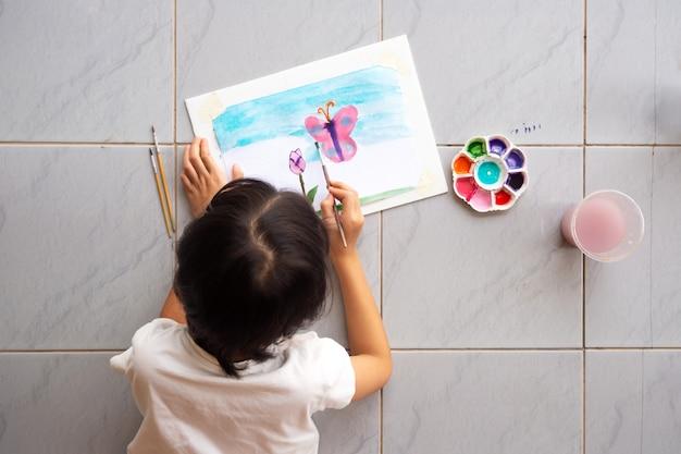 Asiatisches mädchen, das auf bodenmalerei bild durch aquarell niederlegt.