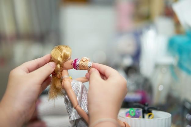 Asiatisches mädchen, das barbie-puppe im raum spielt