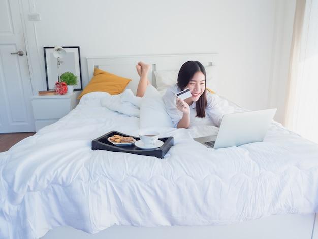 Asiatisches mädchen, das computer mit kreditkarte auf bett verwendet