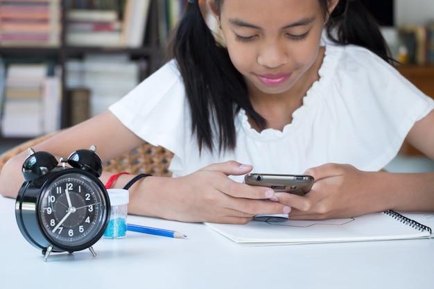 Asiatisches mädchen, das das internet sitzt und sucht, um ihre hausarbeit zu tun