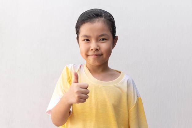 Asiatisches mädchen, das daumen hoch zeichen macht und fröhlich lächelt,