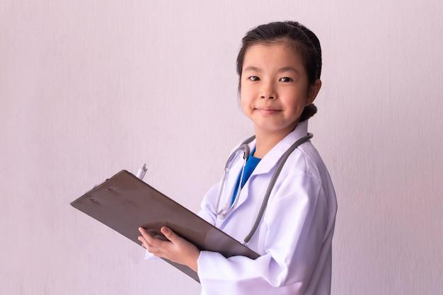 Asiatisches mädchen, das doktor mit stethoskop in den händen spielt und auf zwischenablage schreibt