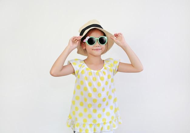 Asiatisches mädchen, das eine sonnenbrille und einen strohhut auf weiß trägt