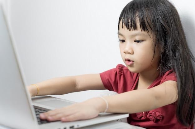 Asiatisches mädchen, das ernsthaft an einer laptop-computer arbeitet. üben mit technologischen geräten.