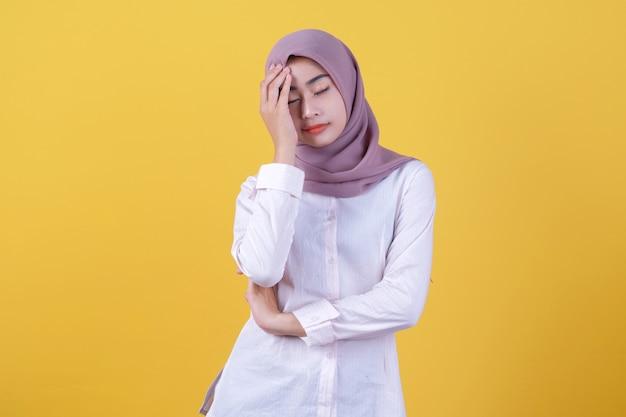Asiatisches mädchen, das etwas auf verwirrende geste zeigt, die hijab trägt