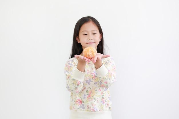 Asiatisches mädchen, das geschälte orange frucht auf weiß hält