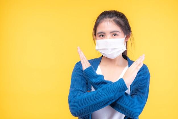 Asiatisches mädchen, das gesichtsmaske trägt, zeigen stop-hand-geste für stop-corona-virus-ausbruch