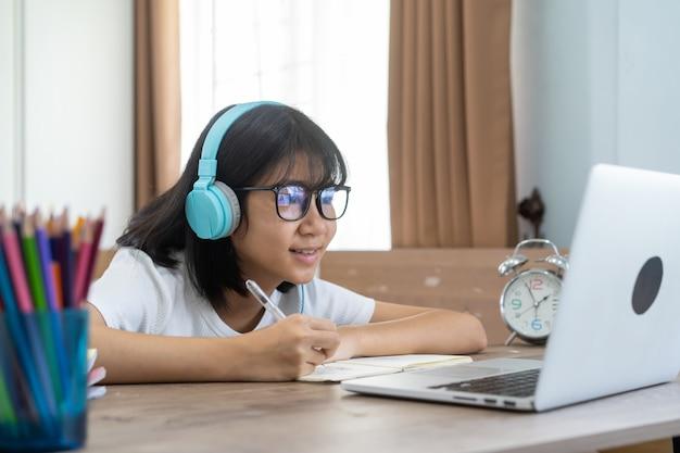 Asiatisches mädchen, das hausaufgaben-online-lektion zu hause studiert, konzept der sozialen distanz-online-bildungsidee