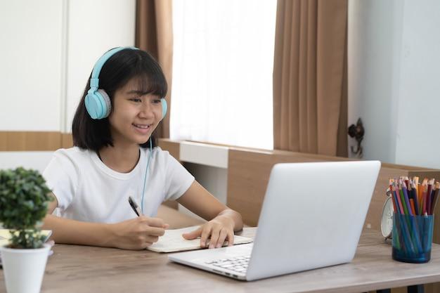 Asiatisches mädchen, das hausaufgaben-online-unterricht zu hause studiert, soziale online-fernunterricht