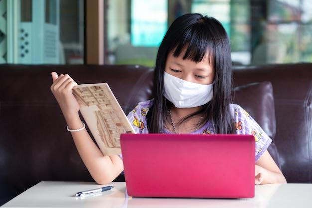 Asiatisches mädchen, das hausaufgaben studiert und gesichtsmaske während ihrer online-lektion zu hause trägt, um das 2019-ncov- oder covid 19-virus zu schützen, online-bildungskonzept.
