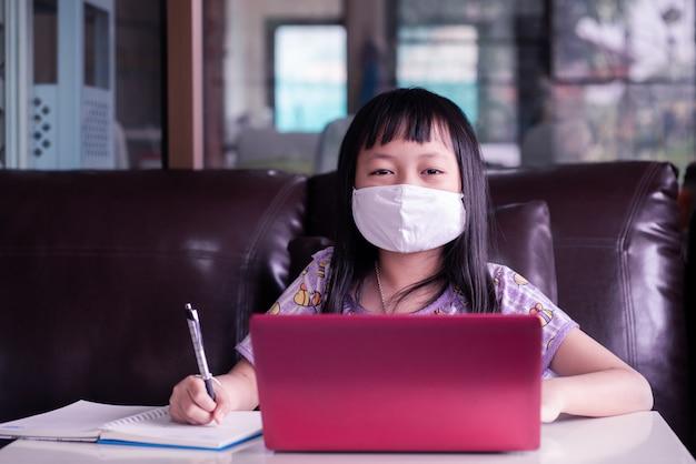 Asiatisches mädchen, das hausaufgaben studiert und gesichtsmaske während ihrer online-lektion zu hause trägt, um das virus 2019-ncov oder covid 19 zu schützen