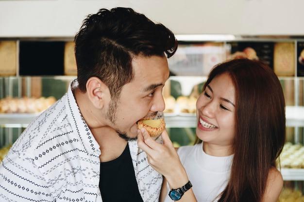 Asiatisches mädchen, das ihren freund speist
