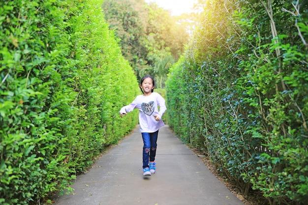 Asiatisches mädchen, das im gartenlabyrinth läuft