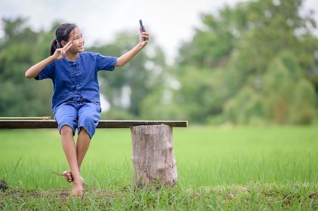 Asiatisches mädchen, das in ländlichen gebieten lebt sie sitzt glücklich in den reisfeldern des ländlichen thailands. lächelndes und glückliches asiatisches mädchen in einem reisfeld mitten in der natur.