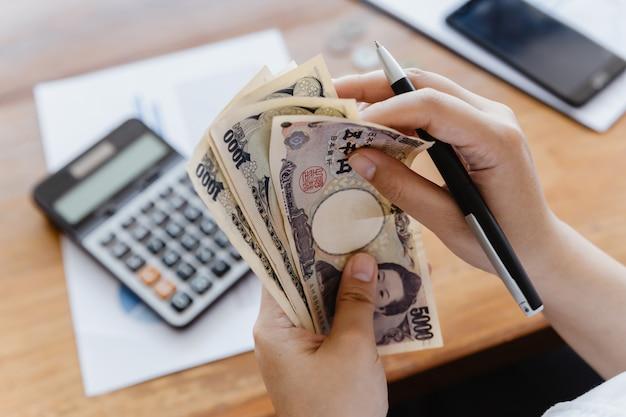 Asiatisches mädchen, das japanischen yen-rechner für persönliche buchhaltung zählt