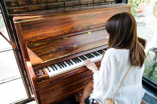 Asiatisches mädchen, das klavier spielt