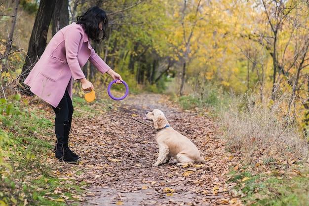 Asiatisches mädchen, das mit ihrem hund im park spielt.