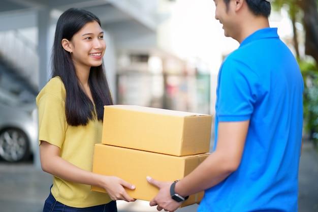 Asiatisches mädchen, das paket vom lieferer, paketverpackung erhaltend empfängt. schnell und zuverlässig