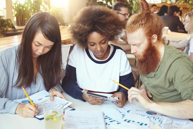 Asiatisches mädchen, das papiere mit graphen und diagrammen ausfüllt, während afrikanische frau ideen mit rothaariger bärtiger kollegin auf touchpad teilt.
