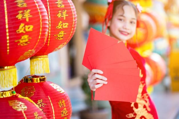 Asiatisches mädchen, das rotes traditionelles chinesisches cheongsam trägt, rote umschläge in der hand und laternen mit dem chinesischen text segen darauf geschrieben hält, ist ein glückssegen für chinesisches neujahr