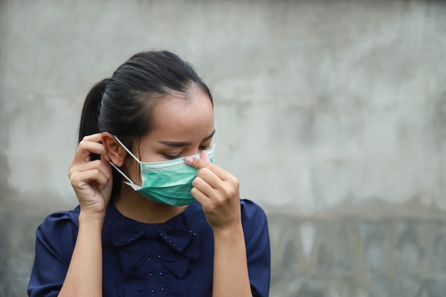 Asiatisches mädchen, das schutzmaske mit kaltfiebergefühl der krankheit für corona-virus-konzept trägt