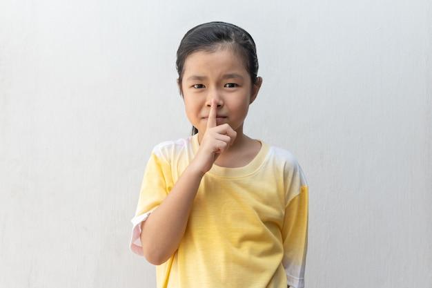 Asiatisches mädchen, das shh zeichen zeigt. bleib bitte ruhig.