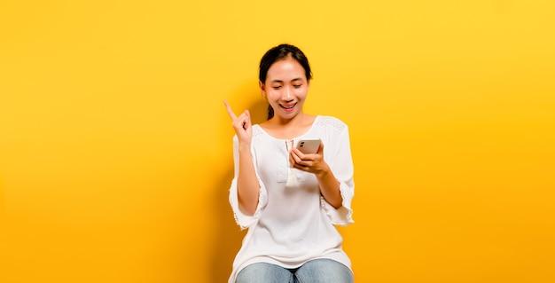 Asiatisches mädchen, das sich glücklich fühlt und auf einem smartphone auf gelbem hintergrund sitzt und tippt Premium Fotos