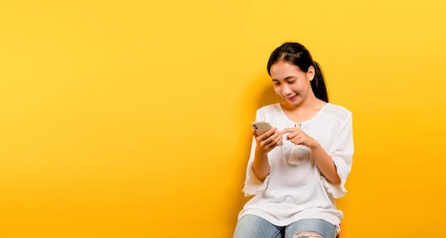 Asiatisches mädchen, das sich glücklich fühlt und auf einem smartphone auf gelbem hintergrund sitzt und tippt